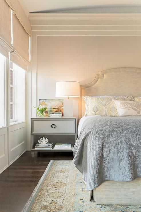 Yellow and gray bedroom features a gray bed dressed in yellow and gray shams and a gray silk quilt atop a yellow and blue rug beside a gray nightstand with one drawer adorned with an oil-rubbed bronze ring pull topped with a white marble lamp.
