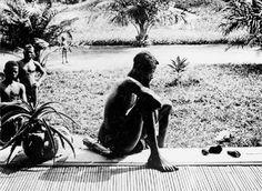Pai olhando para pé e mão de sua filha que foram cortados pelas autoridades policiais do Congo Belga para impedir o roubo e assustar os plantadores para que colhessem mais borracha natural