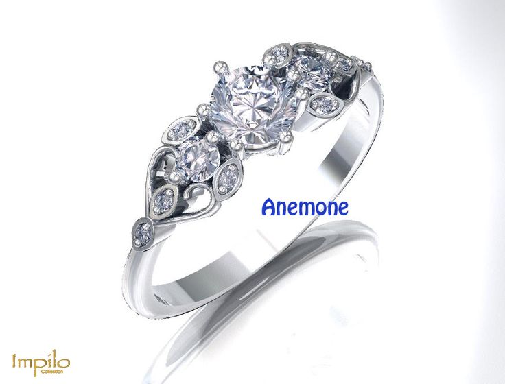 """""""Anemone"""" - Round brilliant cut diamond centre stone with a small round brilliant cut diamond on each side. In the intricate design on either side of the ring are smaller diamonds"""