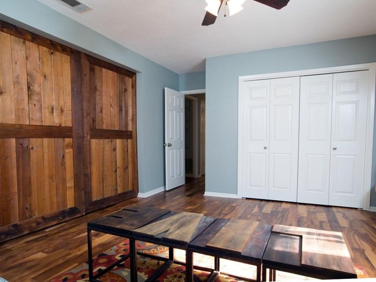Rich hardwood flooring replaces the carpeting throughout the renovation. Here, with its variegated wood tones, the flooring blends visually with the newly installed barn doors and stylized coffee table.