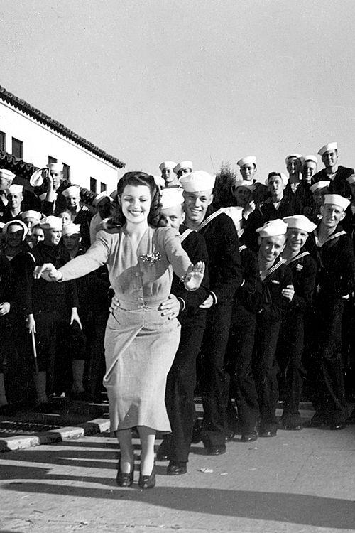 Rita Hayworth leads a conga line of sailors, circa 1941