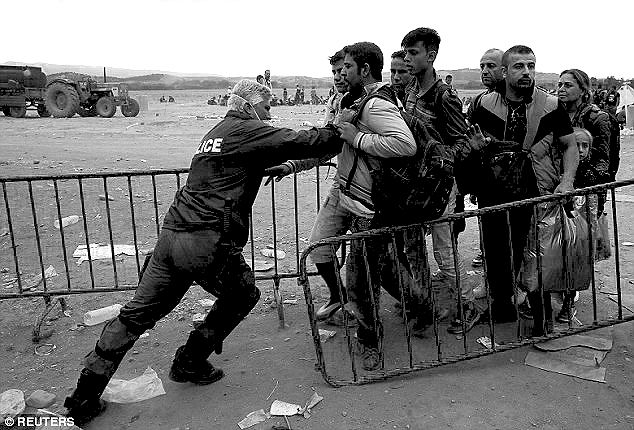 A policeman pushes refugees behind a barrier at Greece's Macedonian border.