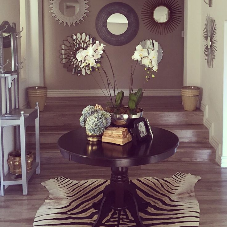 Entryway makeover - zebra skin rug, round centre table with eclectic vignette mixing gold and silver, sunburst mirror collage and silver painted antique hatstand.