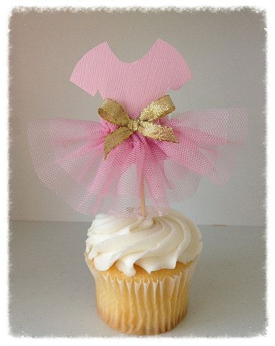 The bodice is soft pink. The skirt is made with fluffy tulle and trimmed with a golden bow.  Celebrate your ballerinas recital or birthday party with these adorable paper cupcake toppers. Place them on cupcakes or a frosted cake for an awesome centerpiece.  Purchase the matching princess crown or decorative wand as shown in the last photos to go with the toppers.