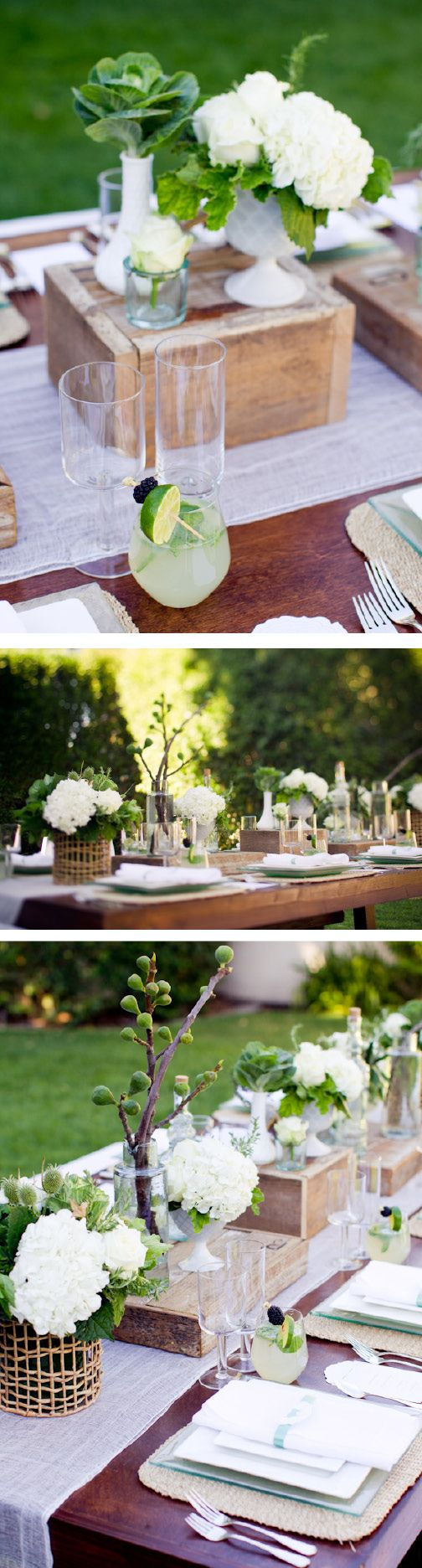 wood farmhouse table with benches and crisp contemporary white seat cushions...cheese cloth as a table runner...modern stemware along with rustic woven place mats, milk glass containers and overturned rustic crates.
