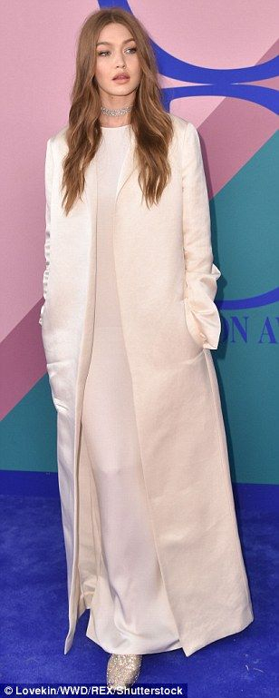 Kisses:Her older sister Gigi opted for a modest ensemble; she layered a white duster coat the floor-length dress by The Row