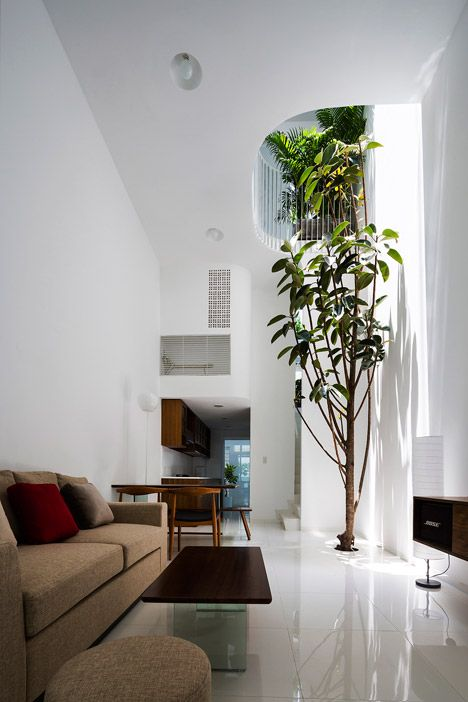 Curving balconies featuring tropical planting wrap a lightwell in the core of this narrow home in Ho Chi Minh City that is just 3.5 metres wide.