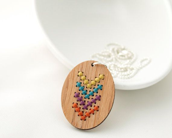 A colorful chevron adorns this modern cross stitch bamboo pendant. Each necklace kit includes: - One bamboo pendant - Stitching chart - Size 28 tapestry needle - Cotton embroidery floss - 19 inch silv