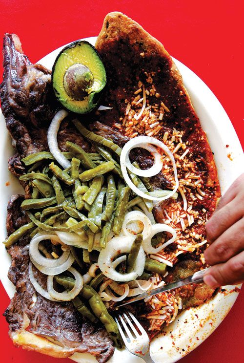 Huarache con Carne Asada: Thick, oblong masa tortillas (named huarache, or sandal, because of their shape) are topped with grated cheese, salsa roja, sautéed steak, and sliced cactus in this classic street food.