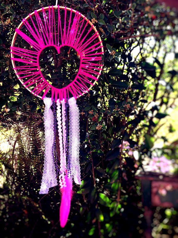 ATRAPASUEÑOS CORAZÓN ROSA  Materiales: Madera, lana rosa fucsia, puntilla blanca, cinta ric rac rosa, cinta de perlas violeta y pluma rosa fucsia  Tamaño: 25 cm diámetro