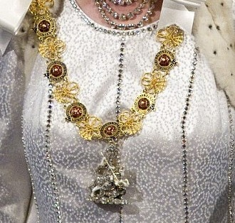 """The Collar of the Most Noble Order of the Garter is a chain of pure gold. The chain is composed of enamel plaques depicting the famous blue garter with the Order's motto, Honi soit qui mal y pense (""""Shame on he who thinks ill of it""""), surrounding a rose which are separated by gold knots. Different Collars may have slightly varying forms of the plaques and knots. The Collar is worn draped over the shoulders."""