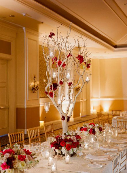 A tree centerpiece covered in candles and flowers