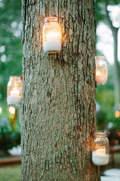 Mason Jars. Mason Jar Lanterns attached to a tree. Tie a ribbon or lace around them to add some glam!
