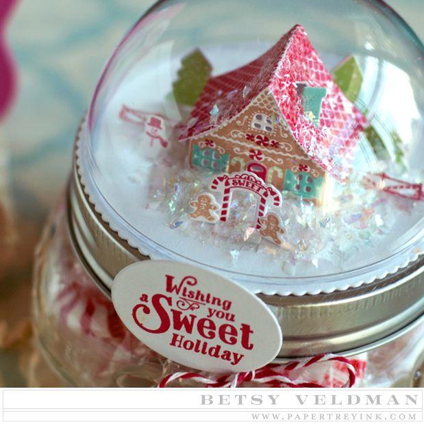 Demi boule en plastique transparent comportant une mini scène en papier d'une maison dans la neige.