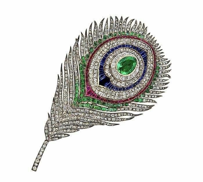 Spilla a forma di piuma di pavone commissionata dall'imperatrice Eugenia poco dopo l'Exposition Universelle del 1867, in oro con diamanti, smeraldi, rubini e zaffiri. La parte centrale può essere rimossa e indossata come un pendente. Maison Mellerio, Parigi.