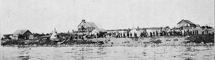 La Loche Mission in 1911   The log building on the right is the rectory. There is a building below the church and one on the left of the photo. Several tepees can be seen. The residents of La Loche are gathered on the shore to welcome their bishop Mgr. Ovide Charlebois. The citizens welcomed Mgr. Charlebois by firing their rifles in the air. This was a common practice when dignitaries arrived and departed. dbutsdunvq00char_0056 (1).jpg (903×253)