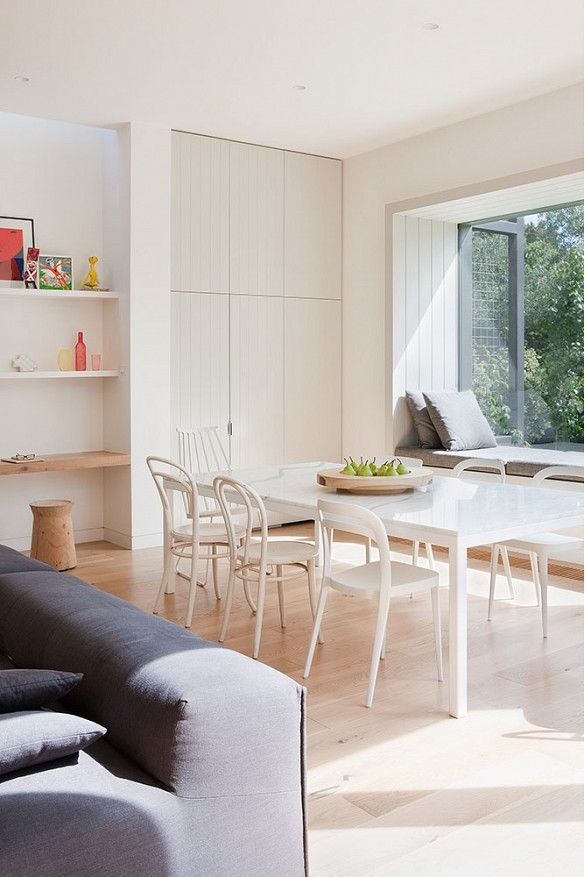 White dining space with open window and moderately empty bookshelves
