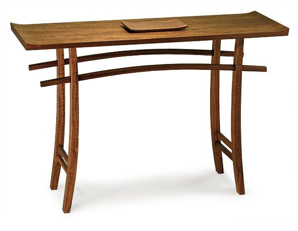 Nick BoyntonBoynton has made several variations of this hall table (16-in. deep by 30-in. wide by 29-in. tall), including dining tables and coffee tables, based on a Japanese Torii arch. This one is curly walnut veneer and solid wood, finished with oil and lacquer. Boynton says people often ask how he mortised the curved stretchers through the curved legs. He bandsawed the parts, laid the stretcher over the legs, and recorded the mortise angle with a bevel gauge. Then he marked how far the…
