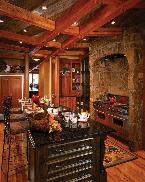 The kitchen is comfortable yet spacious with a beautifully detailed criss-cross timber ceiling paired with the stone surround stove.