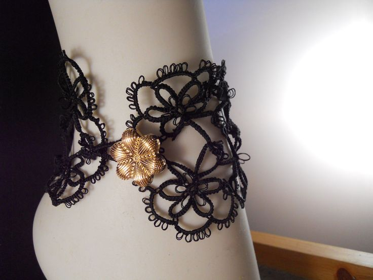 Black ankle cuffs with gold button closure by Mummyearth Designs
