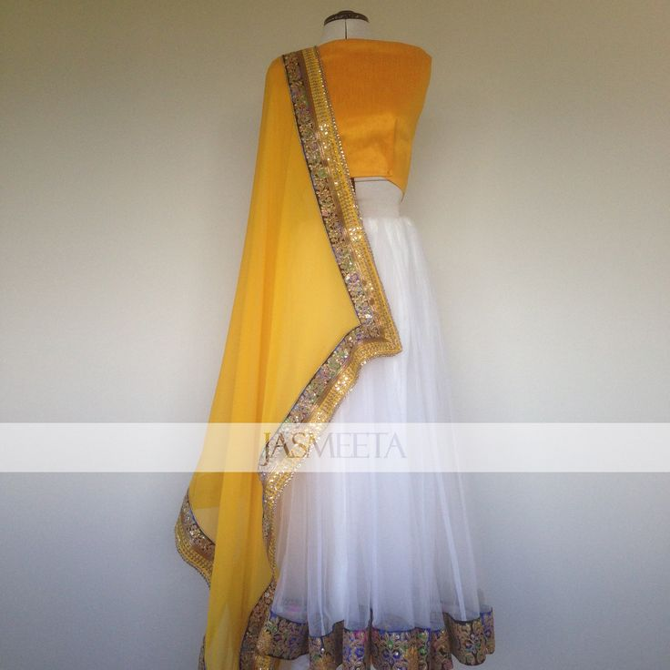 White net skirt paired with a yellow georgette dupatta. Lehenga is semi stitched and will be finished off to your measurements