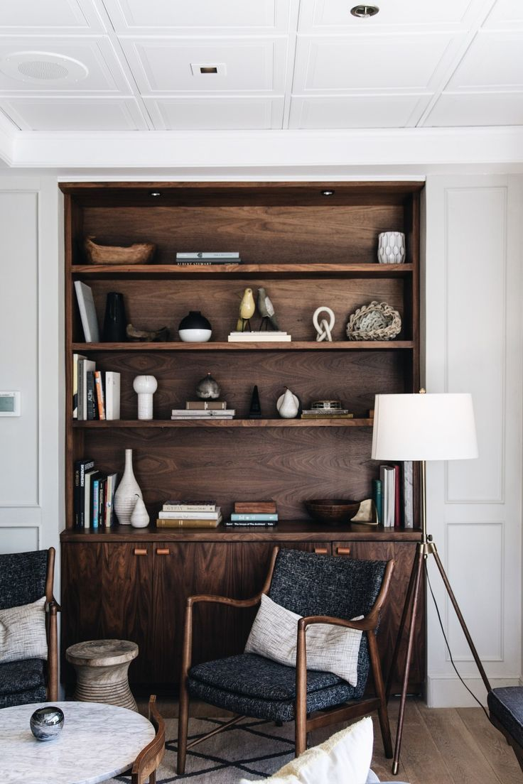 The Landsby, dark wood nookselves, mid-century chairs, marble coffee table, tripod floor lamp, white panelling