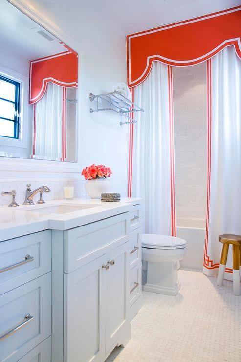 Chic kid's bathroom boasts a drop-in tub dressed in a curved red valance and white and red Greek ...