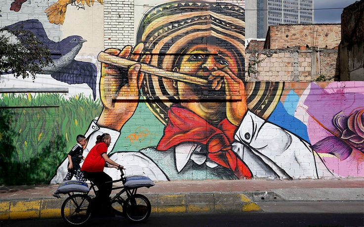 A man cycles past a painting by Colombia's muralist Bulkar in Bogota