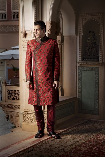 Jamevar achkan style sherwani, highlighted with maroon and green kundan stone by Benzer priced at $1,249