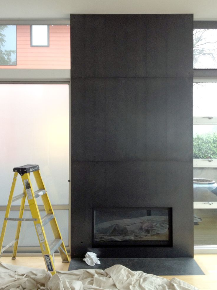 Blackened steel panels wrap the fireplace wall from floor to ceiling. Each  panel was carefully book-matched to trace the natural mill-scale finish  from floor to ceiling. The panels were installed with exposed machine  fasteners.