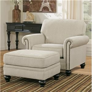 Sophisticated, yet inviting, this upholstered chair and ottoman set in a neutral fabric adds transitional style to your living room's decor. The chair offers the stylish look of rolled arms with nail head trim accents and turned feet in a dark finish. For your comfort, the chair includes a plush loose box seat cushion and attached cushion at its back. The matching ottoman complete the set for a place to prop up your feet or use for extra seating in a pinch.