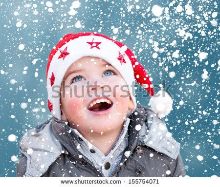 Child with Santa Claus Christmas hat looking at snow falling - stock photo
