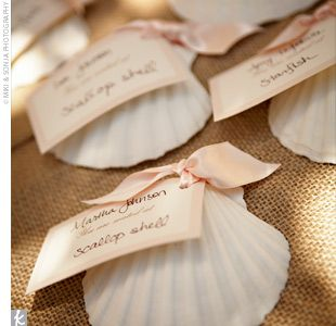 For escort cards the couple used white scallop shells and tied on name tags with pale pink, double-f
