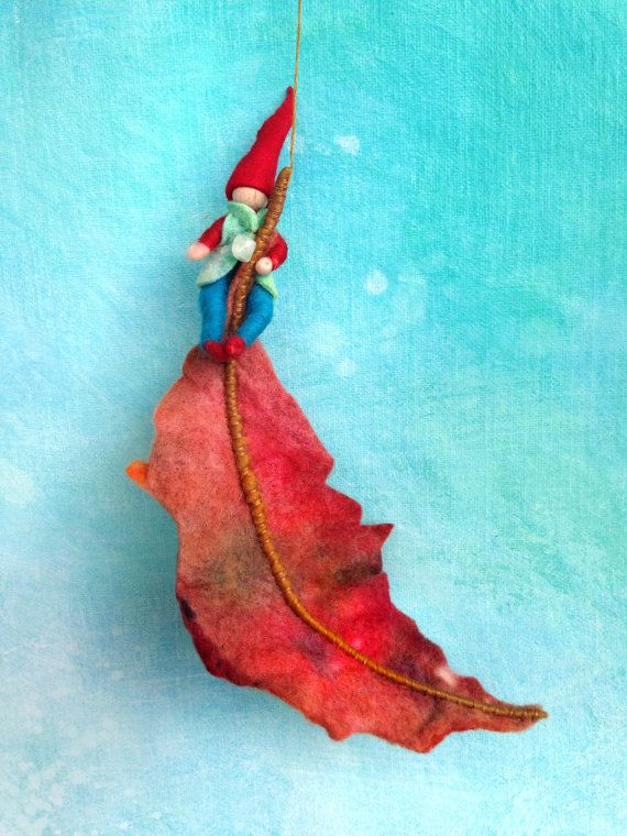 Felt Autumn Gnome on a autumn leaf of wool.  The gnome is sitting on a hanging leaf, the leaf is slightly bendable, and is copied from an oak