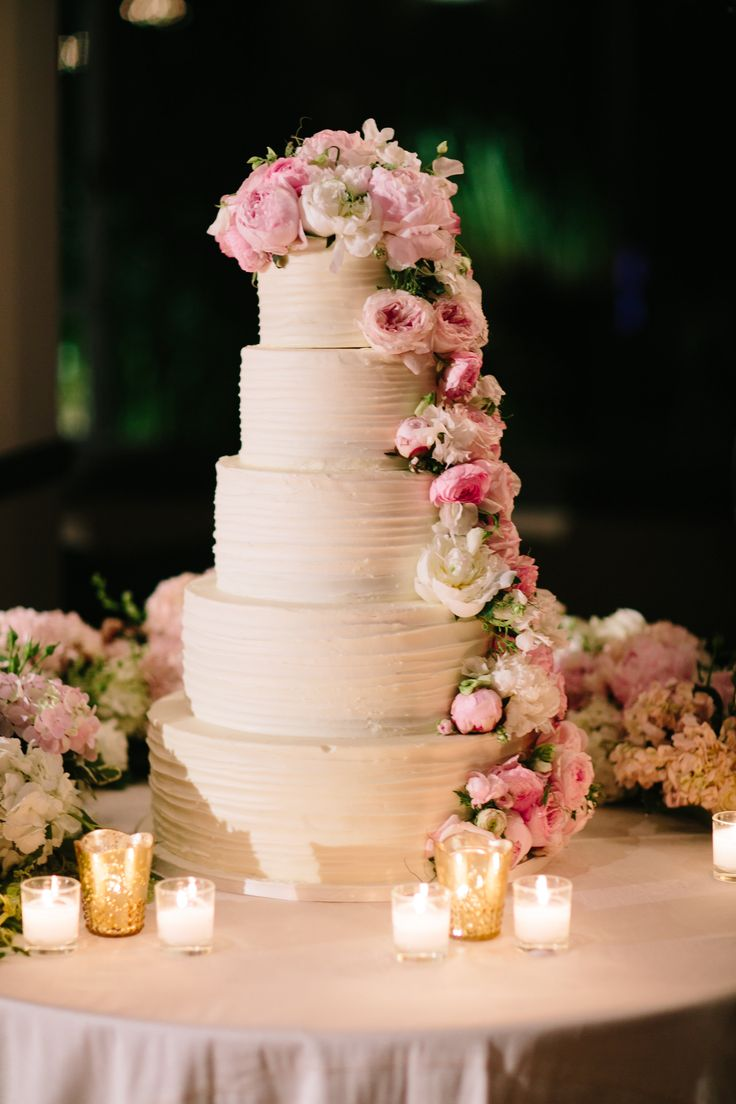 White Cake Decorated with Peonies  Photography: Heather Kincaid Read More: http://www.insideweddings.com/weddings/international-couple-weds-in-floral-ceremony-with-ocean-views/847/