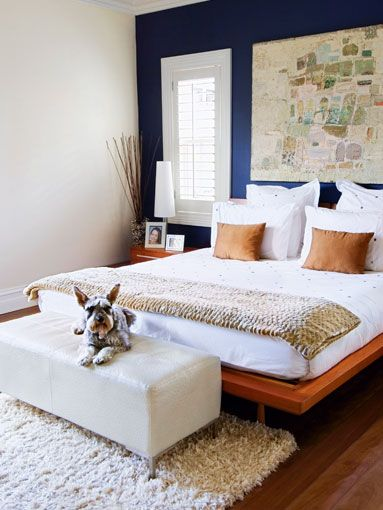 Navy accent wall, white bedding, rug at foot of bed. Now change all camel accessories and white walls to grey.: