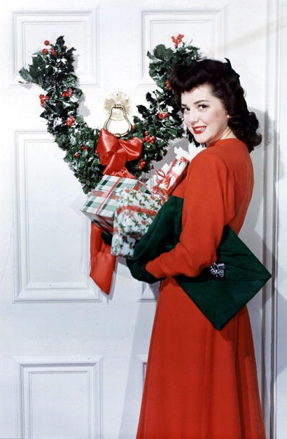 40s red dress winter vintage fashion style movie star black clutch handbag purse color photo print ad Ann Rutherford celebrates Christmas with a Victory wreath.