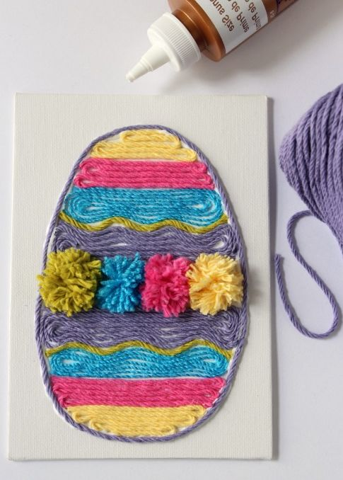 colorful egg collage on white card, shaped like an egg, easter crafts for adults, decorated with yellow, pink and blue pom poms and thread