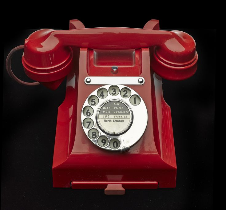 Desktop telephone type 328 of red bakelite, with ten digit dialling ring and pullout tray, by General Electric Co. Ltd, England, c.1940.