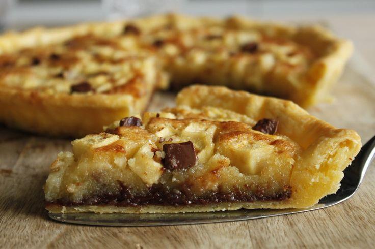 Préchauffez votre four Th.7/8 (220°C). Dans un saladier, mélangez le beurre fondu, la poudre d'amandes et le sucre jusqu'à obtenir un mélange lisse. Ajoutez les œufs et mélangez. Déroulez votre pâte dans un moule à tarte en conservant la feuille de cuisson. Faites fondre 100 g de chocolat au micro-ondes selon le mode d'emploi. Nappez le fond de la tarte avec le chocolat fondu. Recouvrez avec le mélange à base d'amandes. Pelez et coupez les pommes en petits dés puis répart...