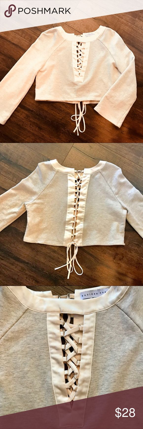 Grey & Cream Crop Top sweater The Grey & Cream Crop Top Sweater features a shiny cream crisscross detailing down the center of the sweater with grey long sleeves. The bow tie at the end of the crop is adjustable! Great condition! Endless Rose Tops Crop Tops