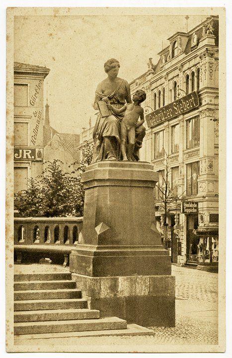 """Königsberg Pr. """"Der Friede"""" Statue am Kaiser Wilhelm Platz.  Im Hintergrund Fa. Gürtler & Hellmann, Glas, Porzellan, Steingut CB"""