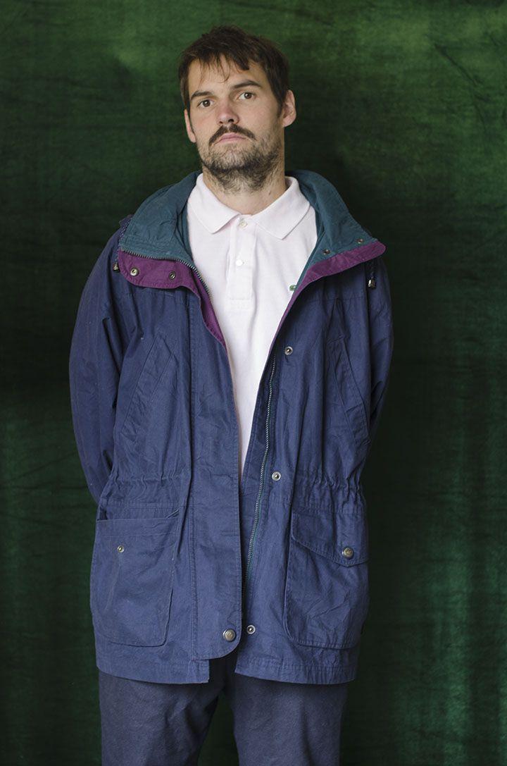 Chaqueta larga en algodón con relleno color azul oscuro con cremallera frontal, cuello alto de color verde, bolsillos frontales a la altura de la cadera. Forro en un poliester azul oscuro.
