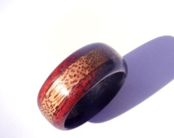 This wooden mens ring is a wood wedding band that has a double Koa band for double the impact! Smooth dark shiny Koa bands fused together gives you a lot of visual appeal since the colors and wood grain in this beautiful wood type is just exquisite! This ring can be worn as a wedding band by unisex adults and is definitely not for men only. If you like the warm rustic appeal of wood you might even want to pair it with a very delicate metal ring, to get a different more feminine look. This…