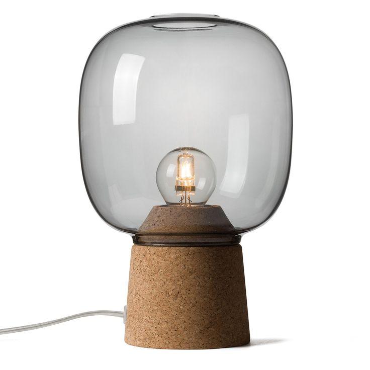 La lampe à poser design en verre Picia, du designer italien Enrico Zanolla, est d'une grande finesse. Le mélange des matériaux -élégance de l'abat jour en verre fumé et naturel du socle en liège - fait de cette lampe à poser un objet qui s'adaptera à n'importe quelle pièce de votre intérieur. Les proportions de cette lampe à poser sont parfaites et le verre fumé donne à cette lampe à poser beaucoup de chic !. <br /> La lampe à poser Picia est disponible en verre transparent, fumé, bleu et…