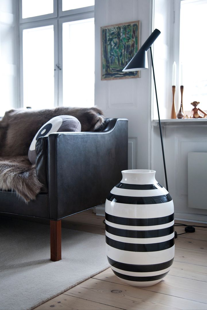 Black leather sofa, fur throw, black lamp and white walls (and a giant striped vase) via 79 ideas