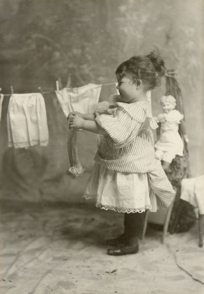 Margery Bish as a little girl wears a striped dress while hanging clothes on a clothesline. There is a doll behind her on the right.