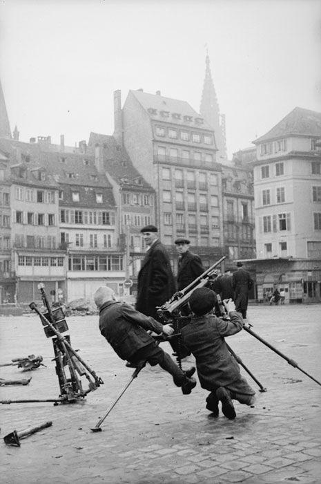 Prise de Strasbourg et sa région par la 2e DB (Division Blindée). Description : Sur la place Kléber à Strasbourg, libérée par les troupes de la 2e DB (Division Blindée) le 23 novembre 1944, des enfants jouent avec un trépied de mitrailleuse allemande MG 34 ou MG 42 abandonné. Date : Novembre 1944 Photographe : Jacques Belin / Roland Lennad Origine : SCA - ECPAD Référence : TERRE-339-L8061
