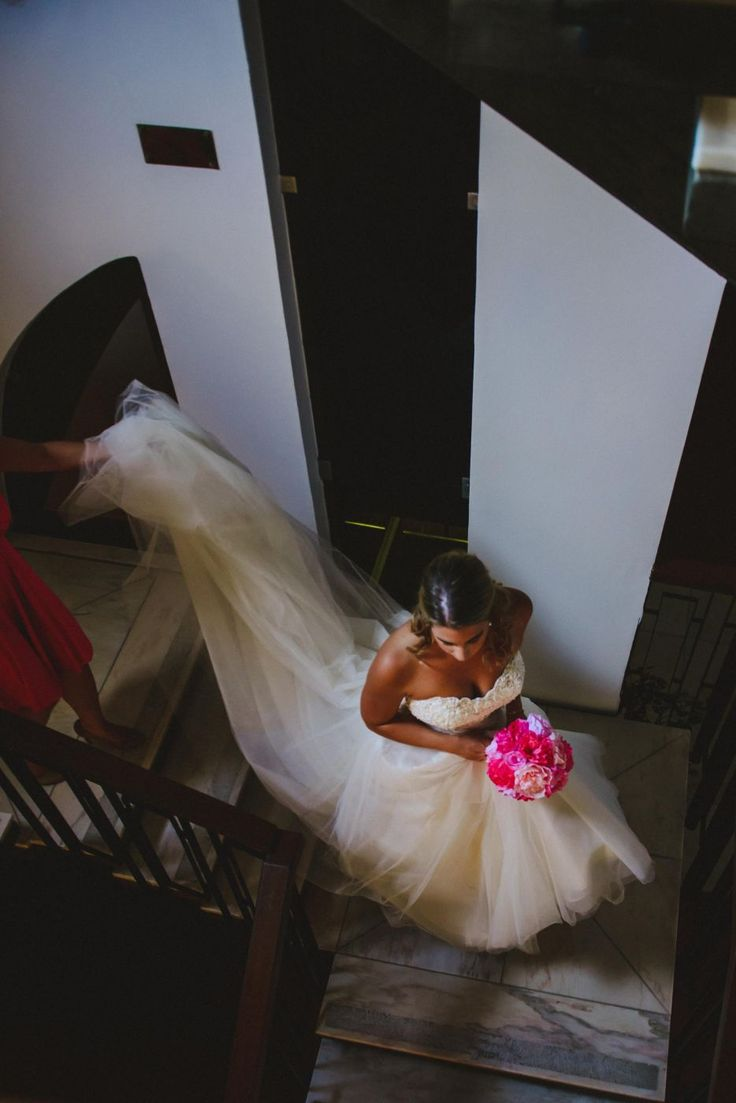 Bride is walking down the aisle in a wedding dress by Privat Lable by G and a pink paper flower bouquet. Cake & Confetti Weddings. Photo by Quemcasaquerfotos