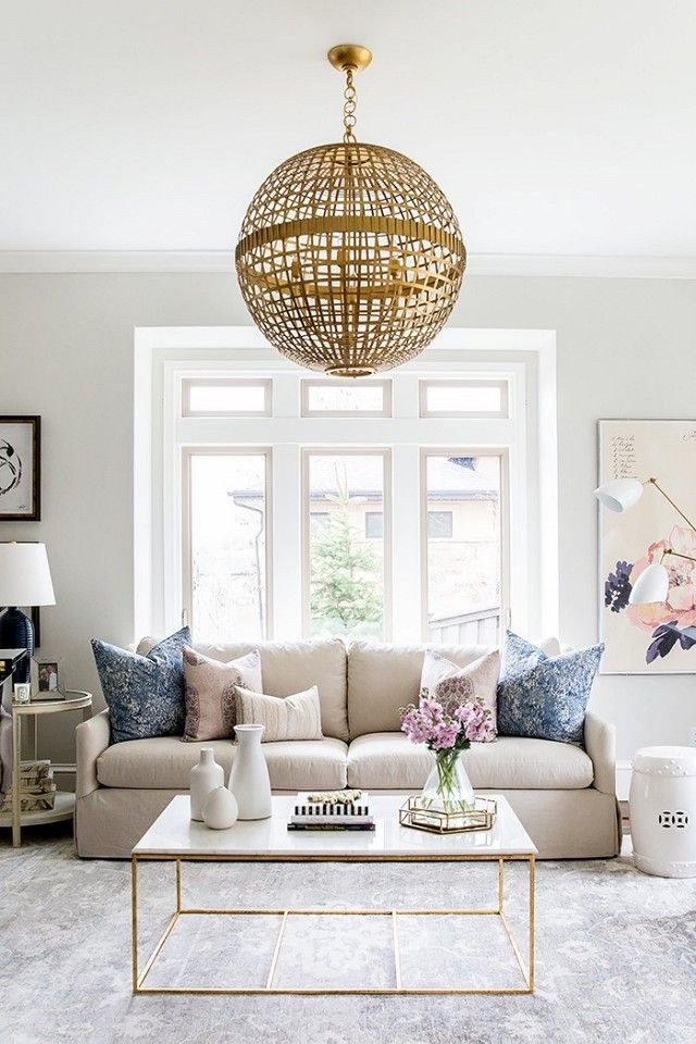 Feminine living space with a large globe gold pendant light, and pastel color pops